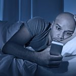 Man on phone at night, which is keeping him awake